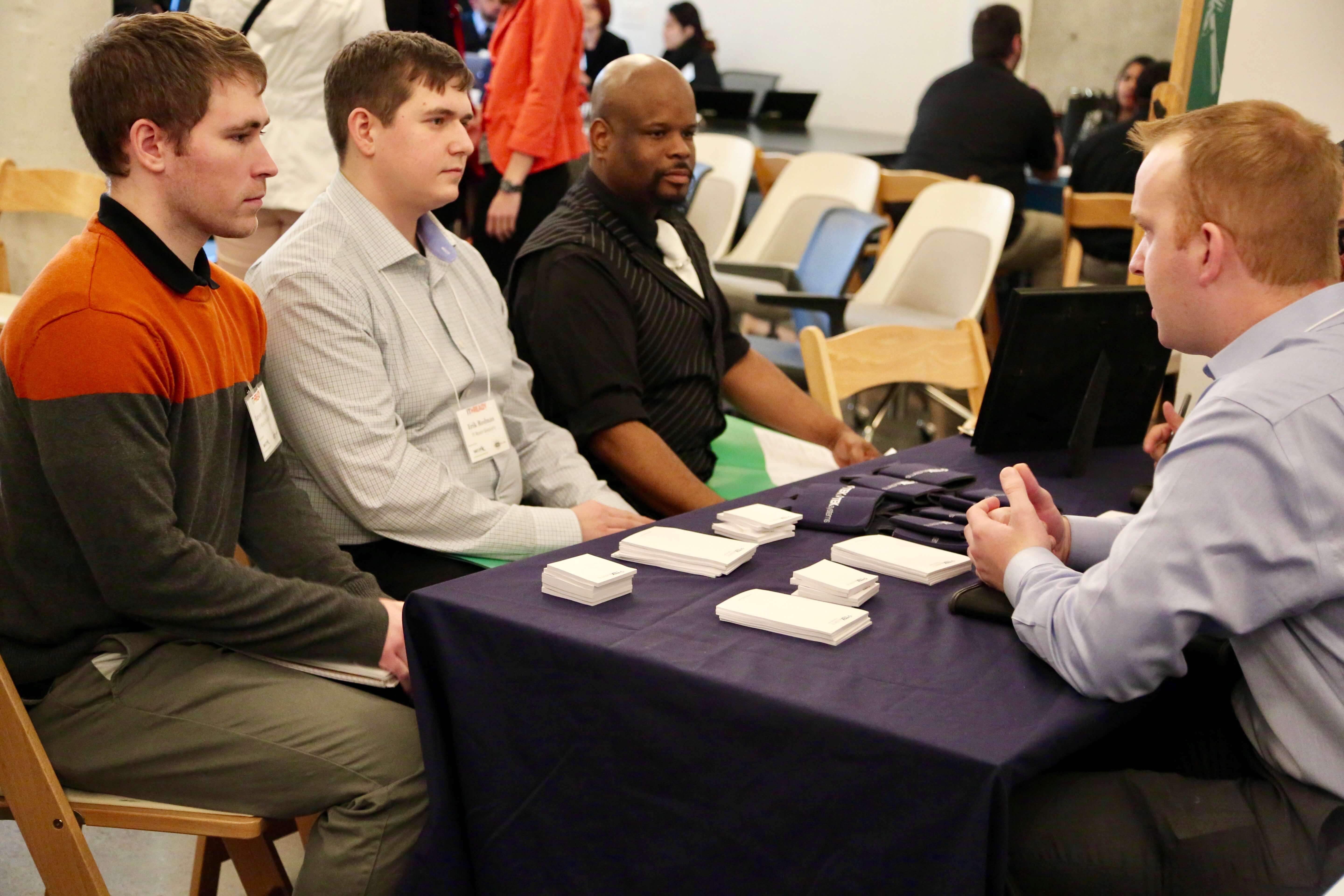TEKsystems talks to graduates during a career fair