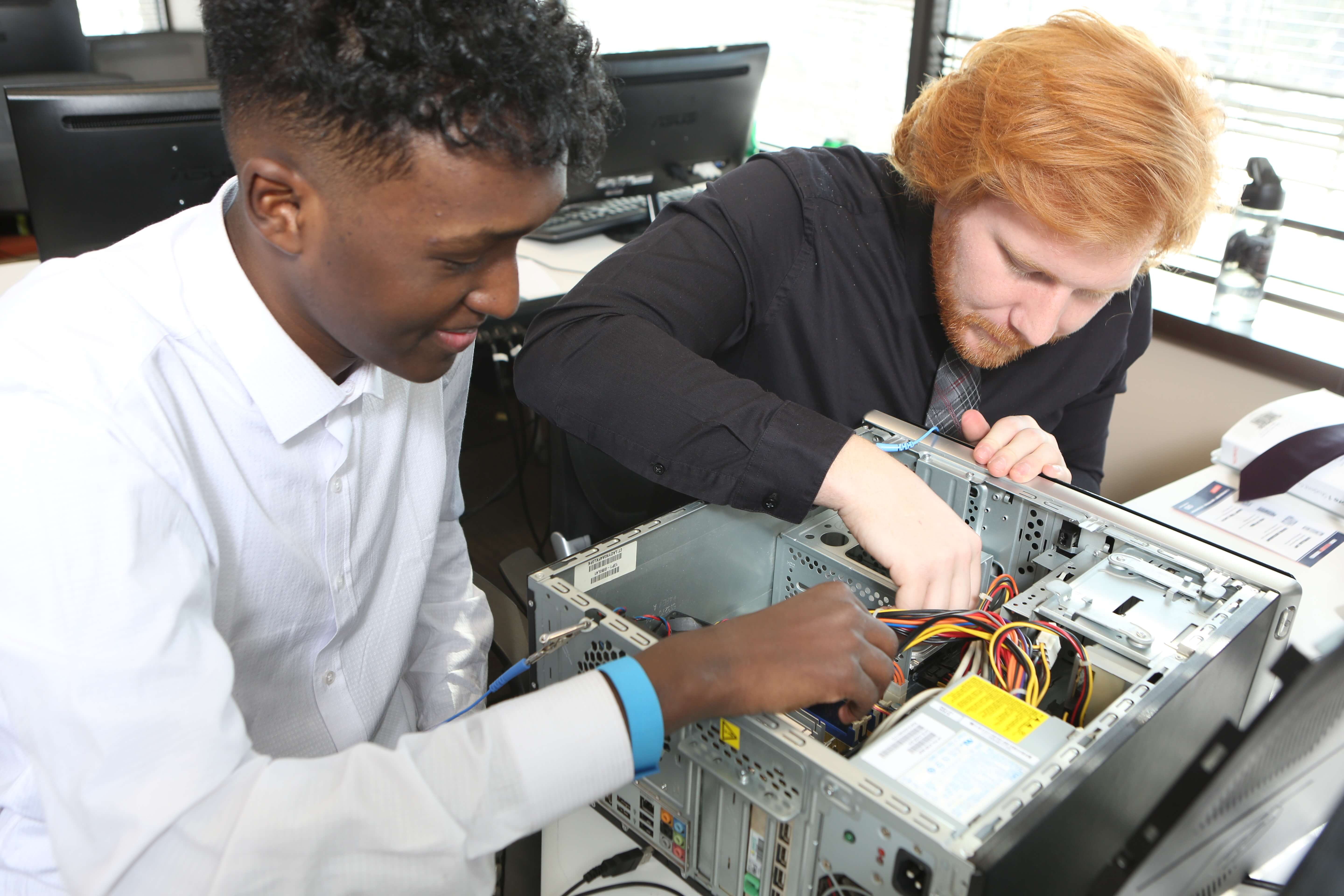 IT-Ready students work on the inside of an open desktop PC